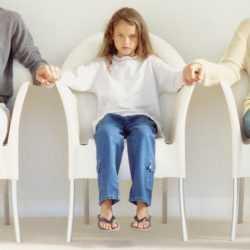 Родители и ребенок сидят в очереди к врачу