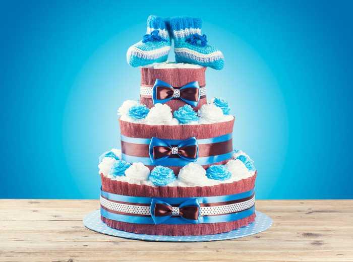 Торт из памперсов в голубом цвете с украшением в форме цветов и пинетками