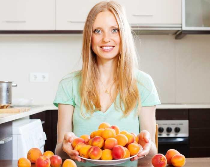 Женщина с абрикосами сидит на кухне