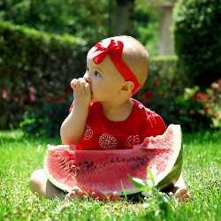 Девочка сидит около большого куска арбуза