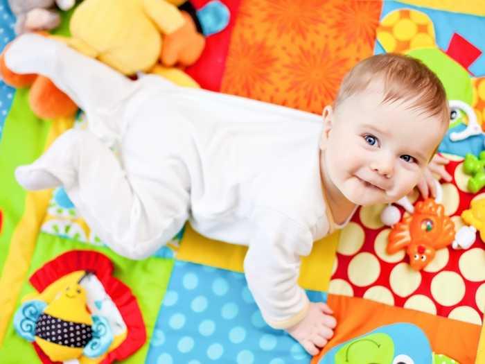 Малыш играет в игрушки на развивающем коврике