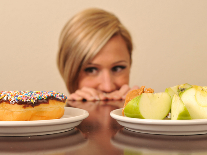 Женщина не может выбрать между пончиком и яблоками