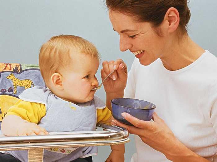 Мама кормит малыша фруктовым пюре