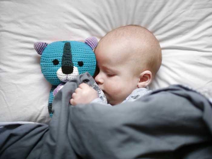 Грудничок спит, обнимая игрушку