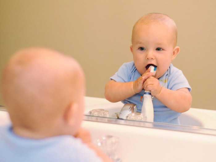 Чистка зубов маленьким ребенком в ванной комнате