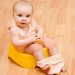 Маленькая девочка сидит на пластмассовом горшке