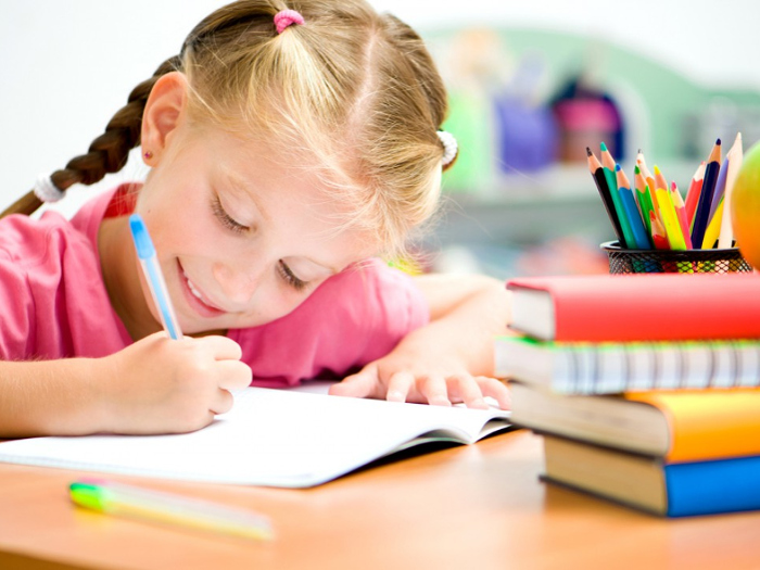 Девочка учится писать ручкой