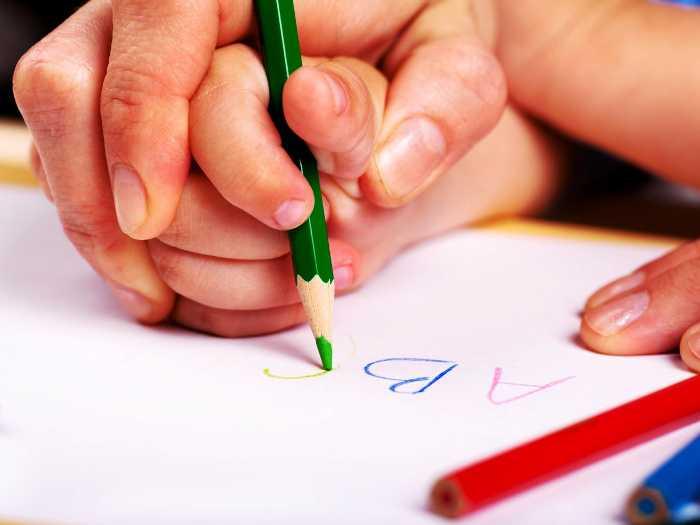 С ребенком занимаются письмом
