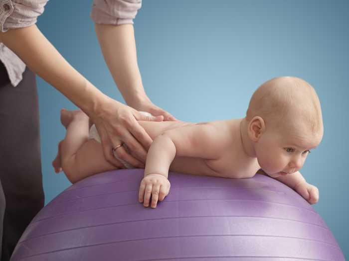 Мама укачивает малыша на фитболе