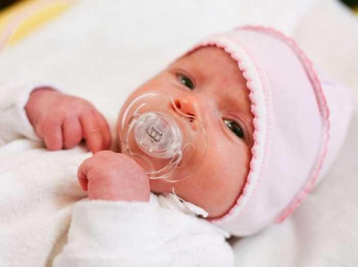Маленький ребенок с пустышкой во рту
