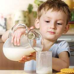 Ребенок наливает в стакан козье молоко