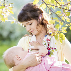 Мама кормит ребенка грудью на природе