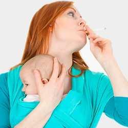 Женщина курит с малышом в слинге
