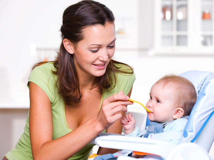 Мама кормит маленького ребенка с ложки
