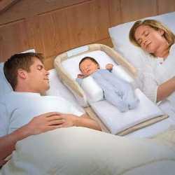 Ребенок в каркасе для сна спит рядом с родителями
