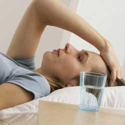 Женщина с головной болью лежит в кровати