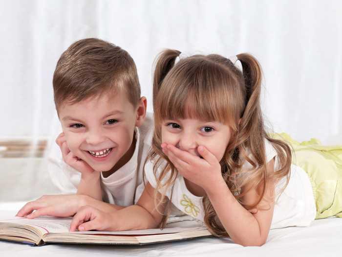 Мальчик и девочка читают книгу