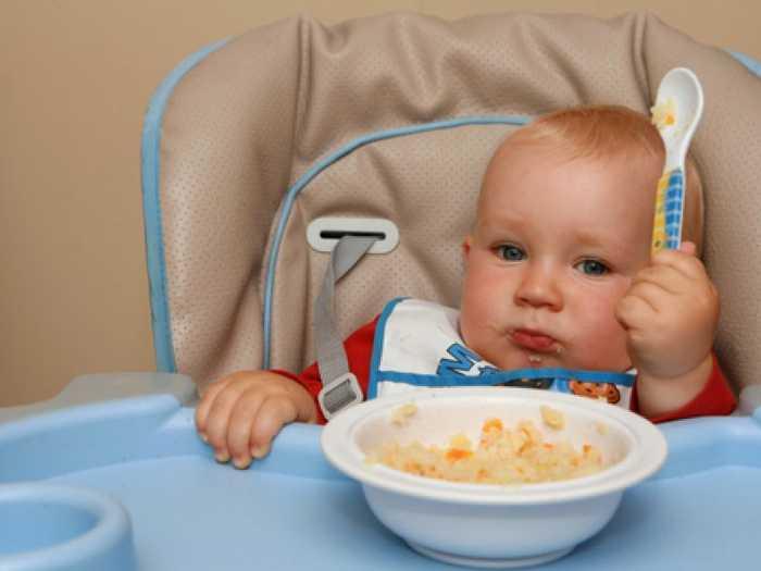 Ребенок ест кашу с овощами