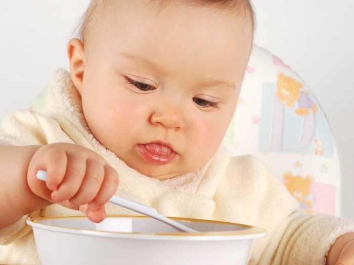 Маленький ребенок кушает кашу
