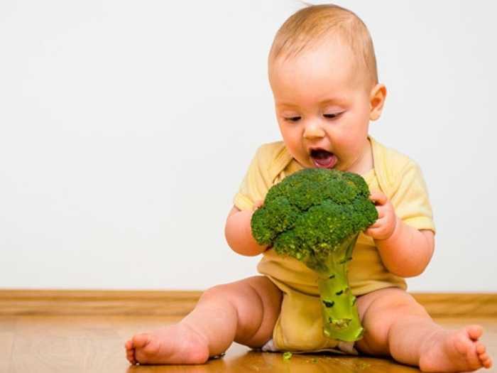 Малыш играет с капустой брокколи