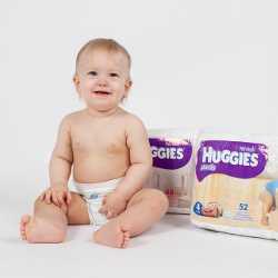 Мальчик сидит рядом с упаковками подгузников Huggies