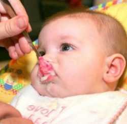 Ребенка кормят с ложки молочной кашей