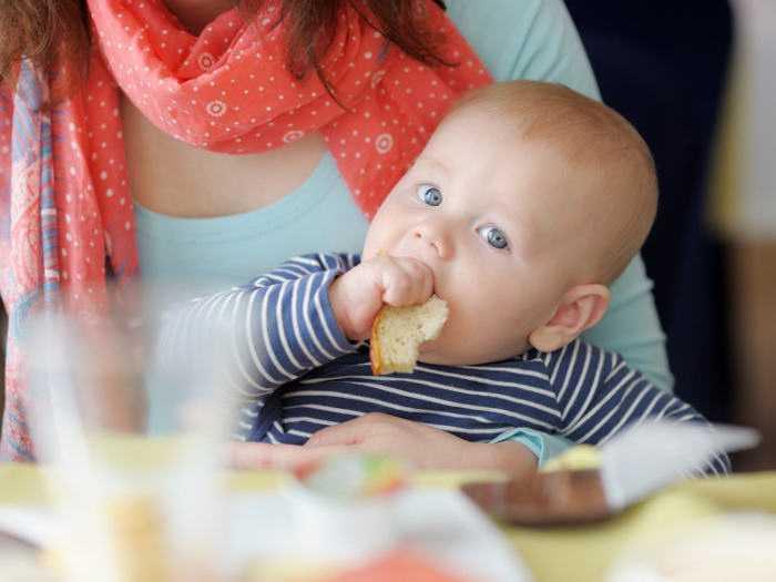 Малыш жует хлеб на руках у мамы