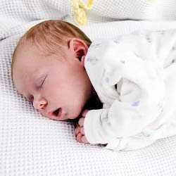 Новорожденный малыш спит на боку