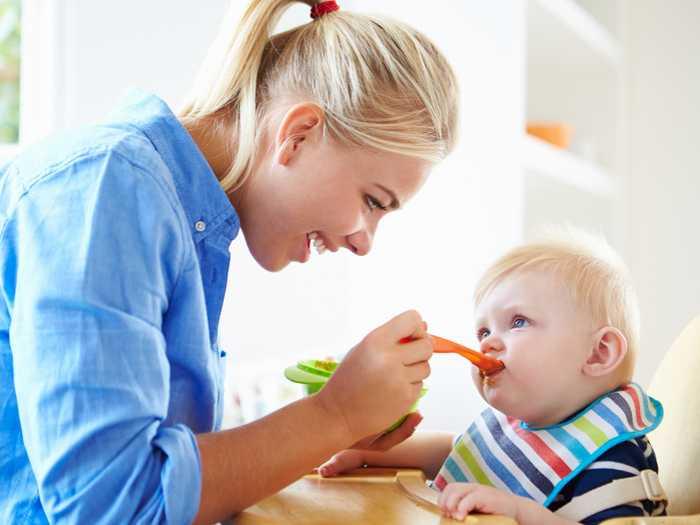 Мама кормит малыша с ложки