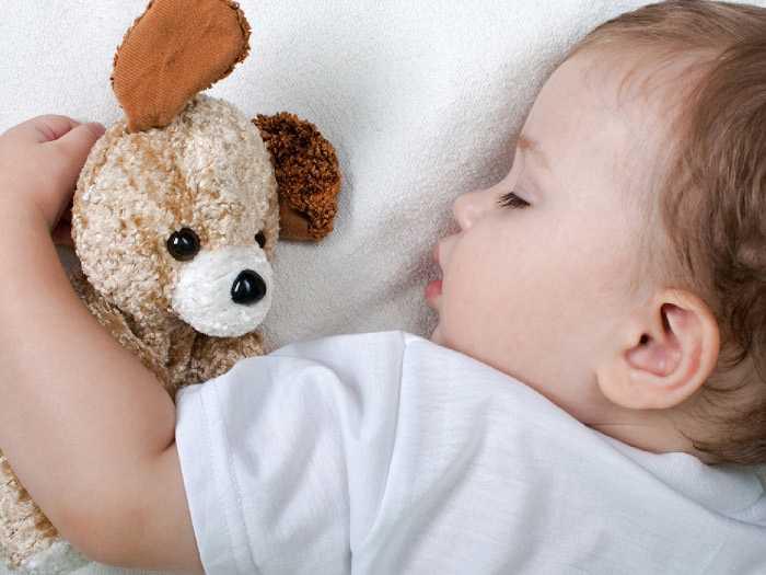 Ребенок спит и обнимает плюшевую игрушку