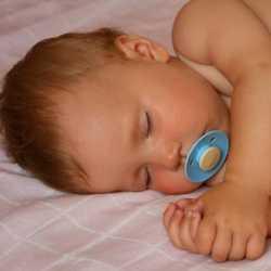 Ребенок спит на кровати с соской