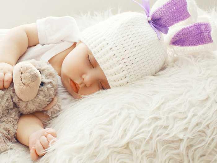 Ребенок спит в шапочке и с игрушкой