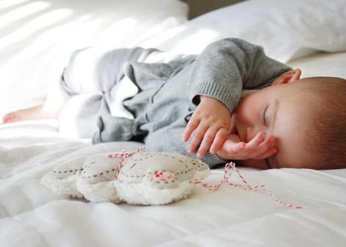 Малыш спит с пальцем во рту и игрушкой