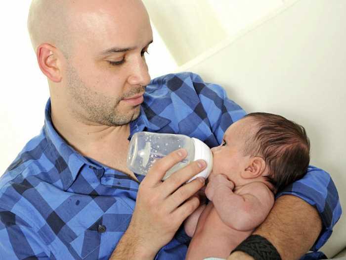Малыш ест из бутылки на руках у папы