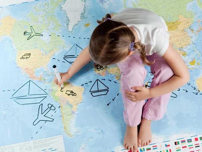 Девочка рисует на карте маршрут путешествия