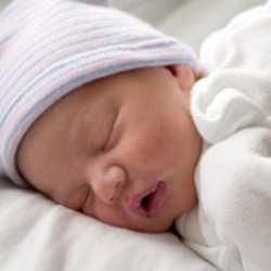 Новорожденный малыш в шапочке и царапках