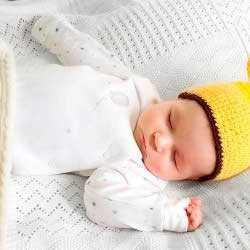Новорожденный спит в кроватке, лежа на спине